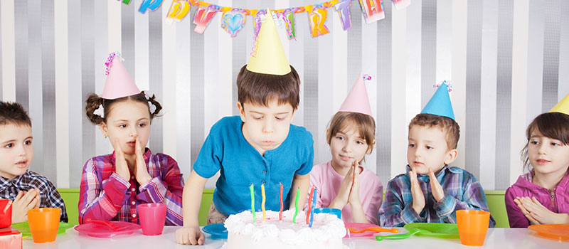 Young Boy Blows Out Candles With Friends